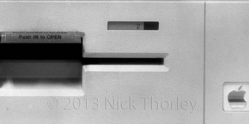 close up crop of large format photo of an old apple e2 floppy drive. photo shot on 8x10 paper negative.