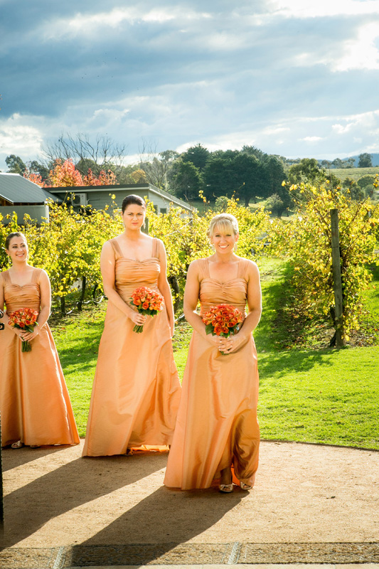 Three brides maids dressed in peach coloured dresses, are shown entering the chapel at Immerse winery.