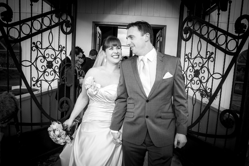 Bride and groom are shown exiting the chapel, with the chapel gates in the back ground. Photo is black and white.