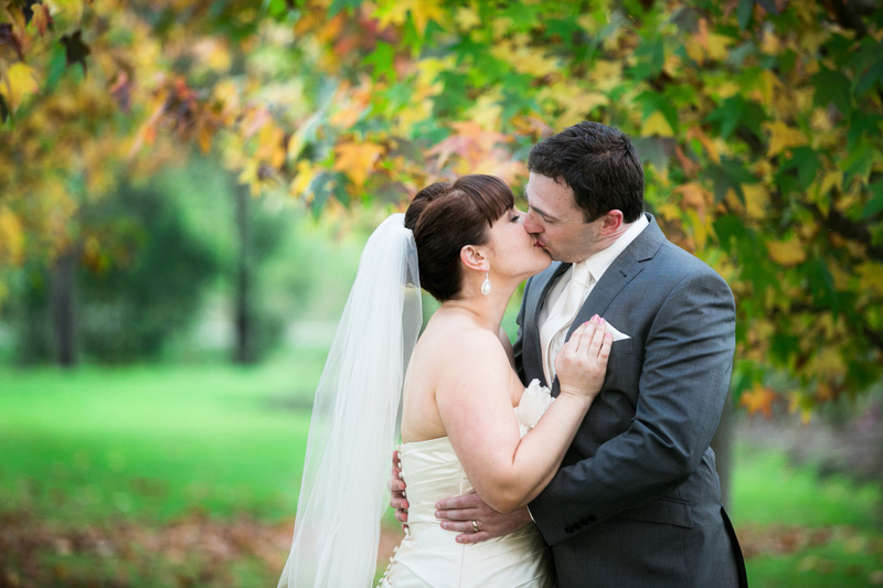 Bride and groom kiss in front of yellow and green tree leaves.