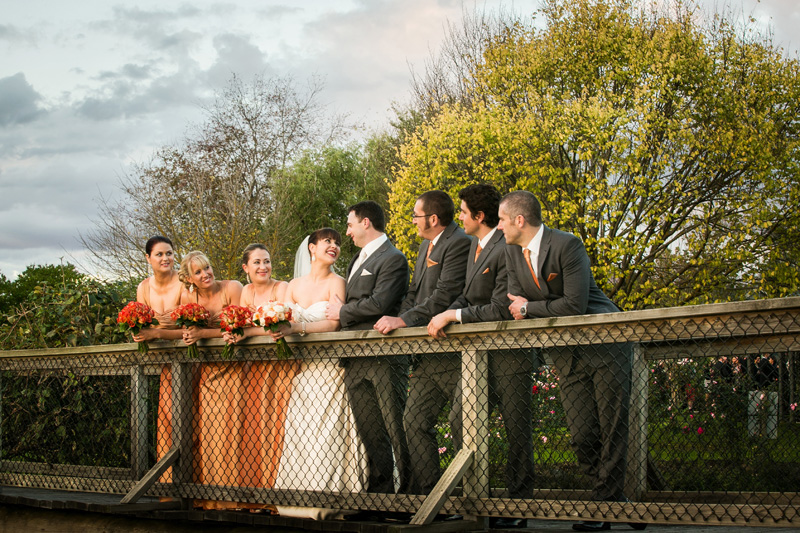 The bridal party are shown leaning on the bridge over the lake out front of Immerse.