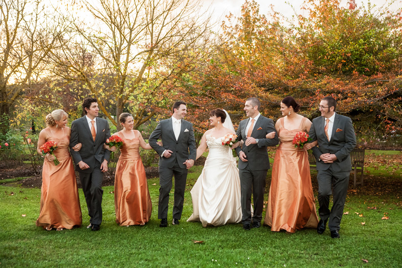 Whole bridal party walk through the garden, with arms linked. Background shows red and green leaves.