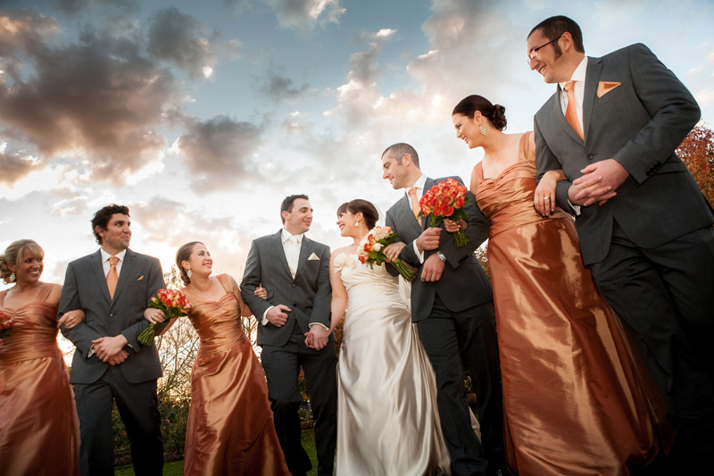 Bridal party walk with arms linked. The background is a cloudy sky with sunset light.