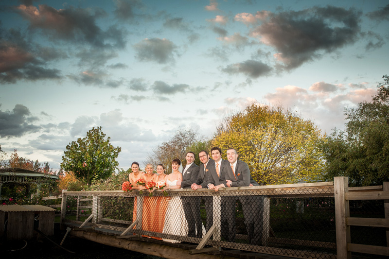 This bridal party of eight people are shown standing on a bridge in Dixons creek. This photo includes sunset light and patchy clouds.