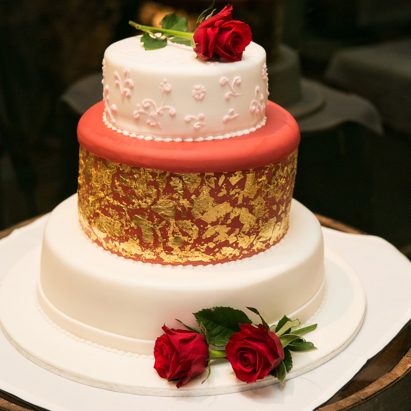 Wedding cake with gold leafing and a rose.