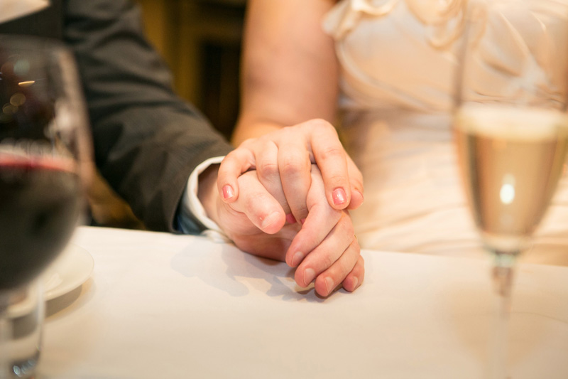 Close up of the bride and grooms hands. They are holding hands on the table at reception.