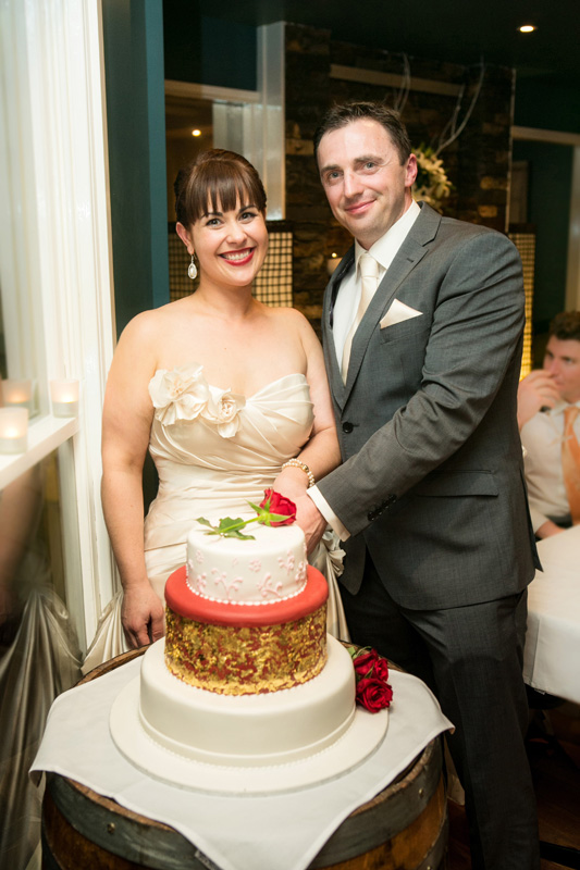 Portrait of the wedding couple cutting the cake.