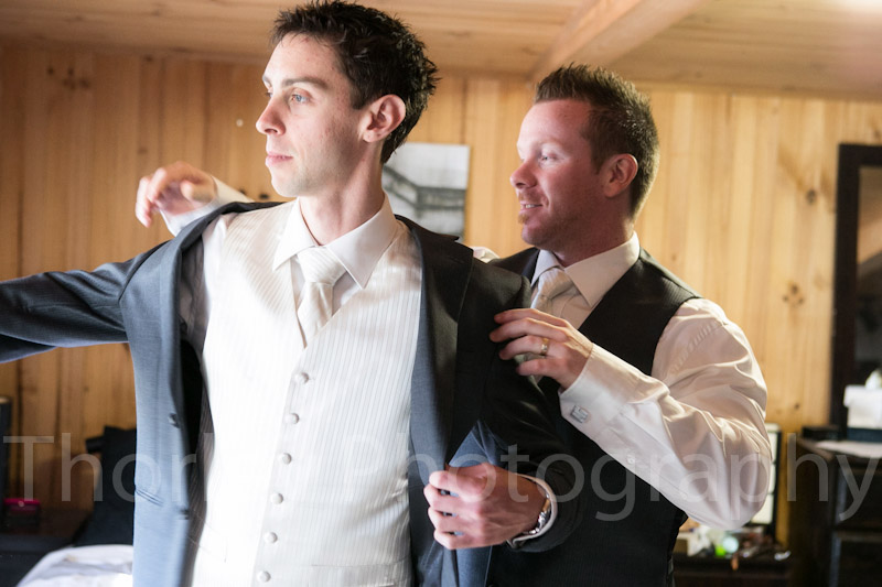 Best man helps groom with his jacket.