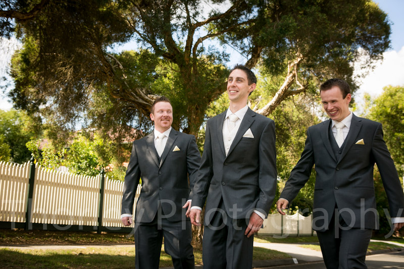 Three groomsmen walking down the street.