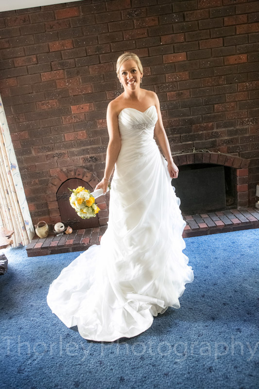 Photo of bride full length in her lounge room on the morning of her wedding.