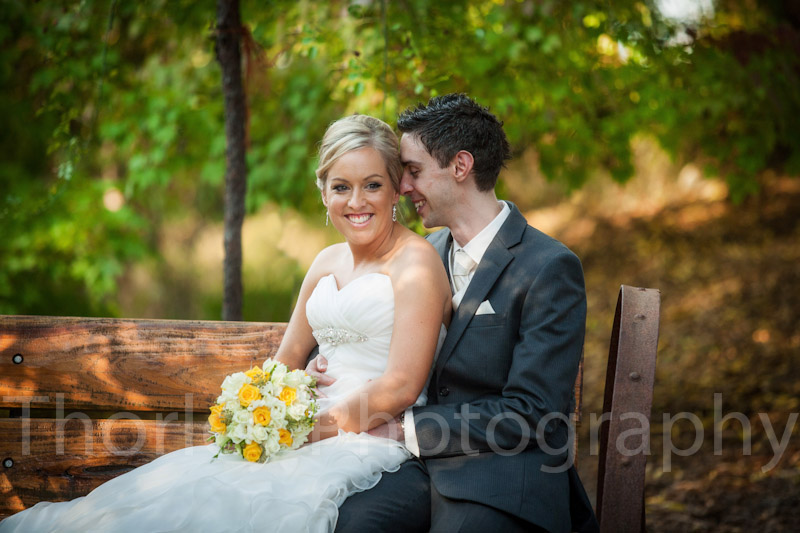 Bridal couple sit in old wooden wagon seat.