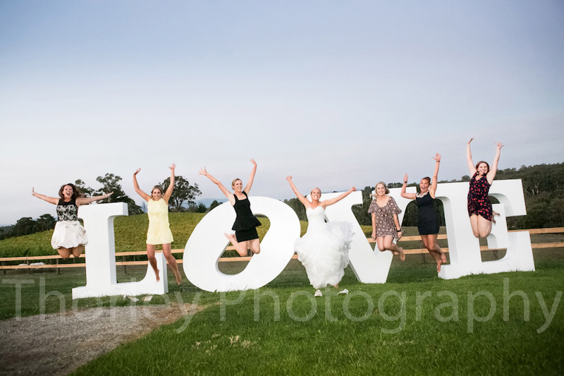 Lots of girls jumping for a photo in front of the love sign.