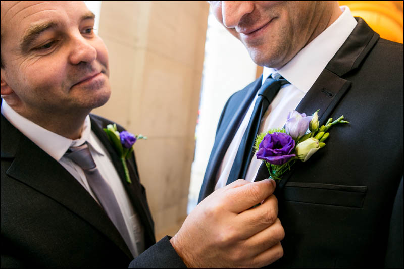 best man fixes the grooms button whole.